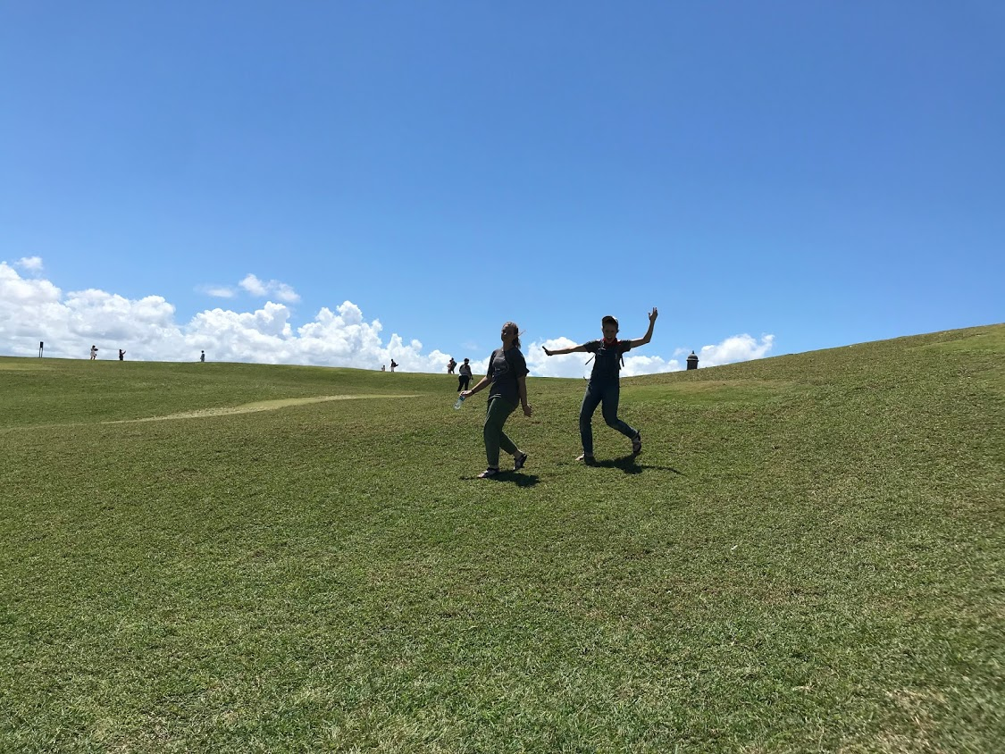 Megan Kucera and Bekah Wommack run around on a hill outside of a fort in Old San Juan while Ben Gourley explores the inside