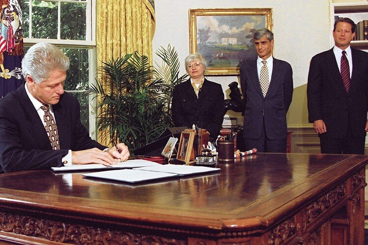 President Clinton signs legislation with Council of Economic Advisors Chair Janet Yellen in the background. (Credit: STEPHEN JAFFE/AFP via Getty Images)