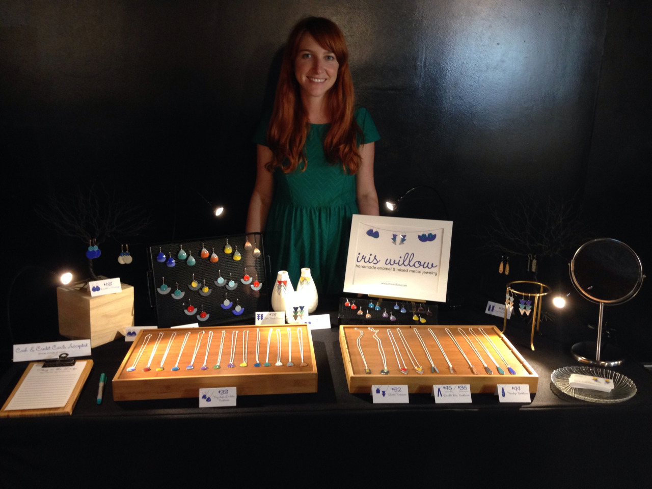 I had a great time last night selling jewelry at Chillin' Productions Anniversary event at the Mezzanine. The place was packed with artists and shoppers alike and had a super fun party vibe with DJs and live painters doing their thing on stage.   It was my first craft show, so I was excited to show off the jewelry displays that'd I'd been working hard on in preparation for the show. I sourced many of my display items from a handful of thrift stores in the Mission. I repurposed two wooden utensil organizers into trays to display my brand new enamel necklaces (coming soon to  my shop ). I also found that mesh office organizers work fantastic as earring holders. I pulled it all together with a couple of super cool wire trees that I bought from an artist selling them on the street back when I lived in Santiago, Chile. They're a tad hard to see in the photo since they blend into the background.    Lighting was something I decided to add last minute, and I'm so glad I did. The space was super dark, so I would have been in a heap of hurt without out the little lamps I added. I was also lucky to be placed next to a fellow jeweler, Valerie Preston of  Valerie Preston Design  who had an amazingly well-lit display to show-off her lovely dream-catcher inspired jewelry. So that, plus my little lamps allowed my jewelry to be seen.    I had a great time at this show and hope to participate in more in the near future. Stay tuned for new dates.