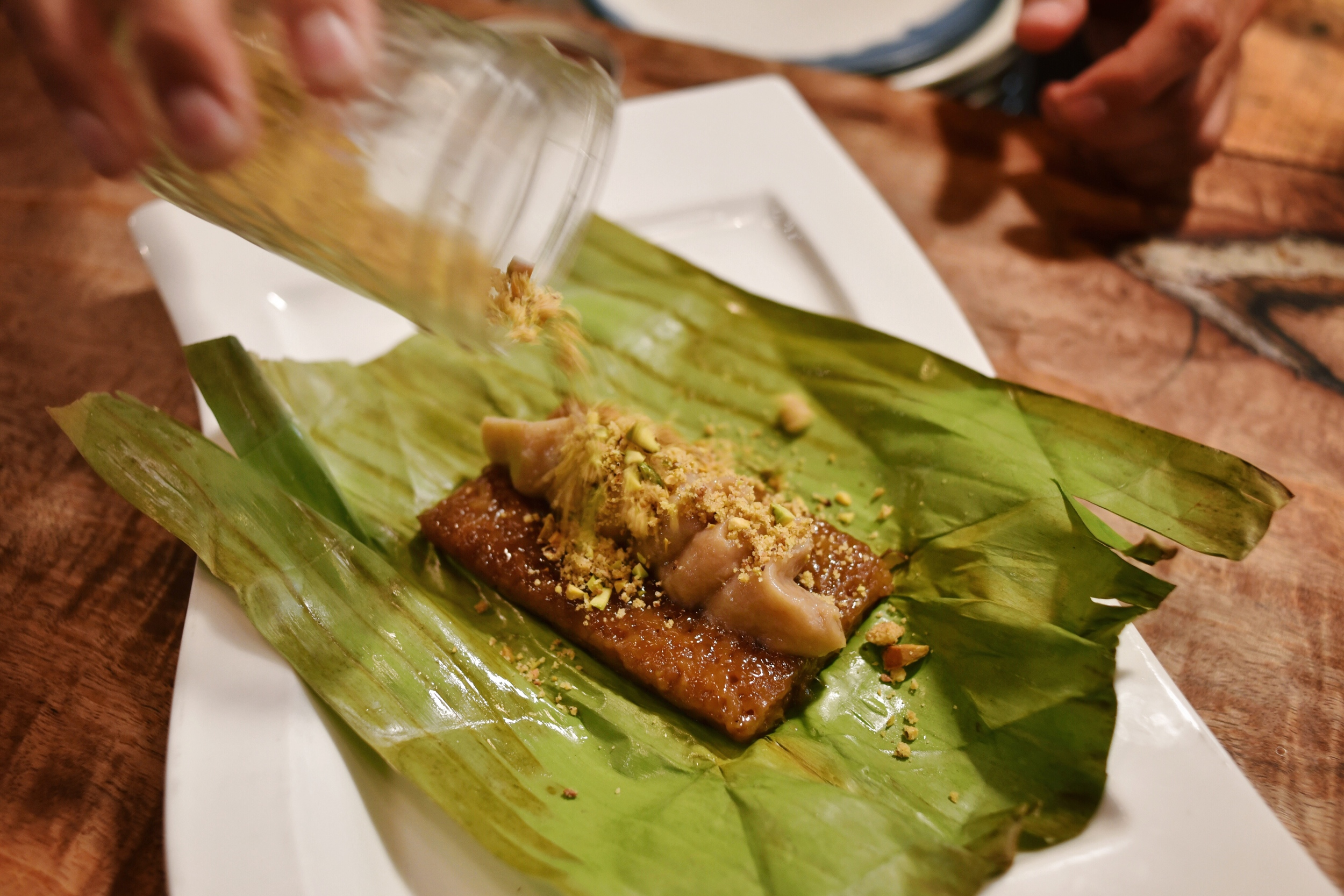 SMOKED BANANA SUMAN, warm coconut sweet rice cake, smoked banana butter and roasted pistachio crumble