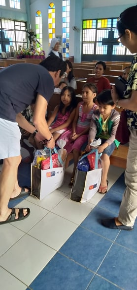 Fr. Kenny giving groceries to the children of Cararayan.jpg