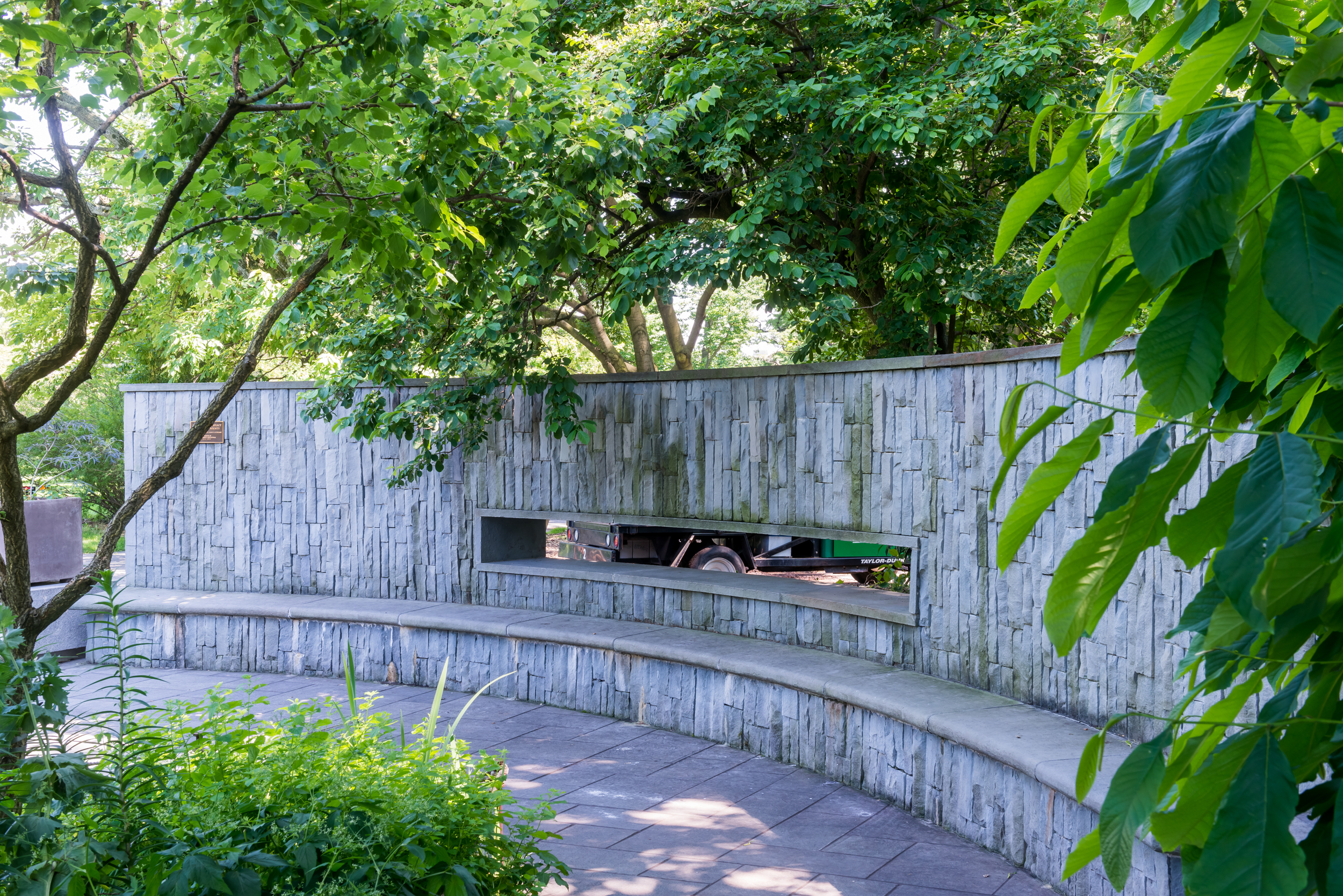 Curved bluestone wall with built-in seating bench and peekabo window