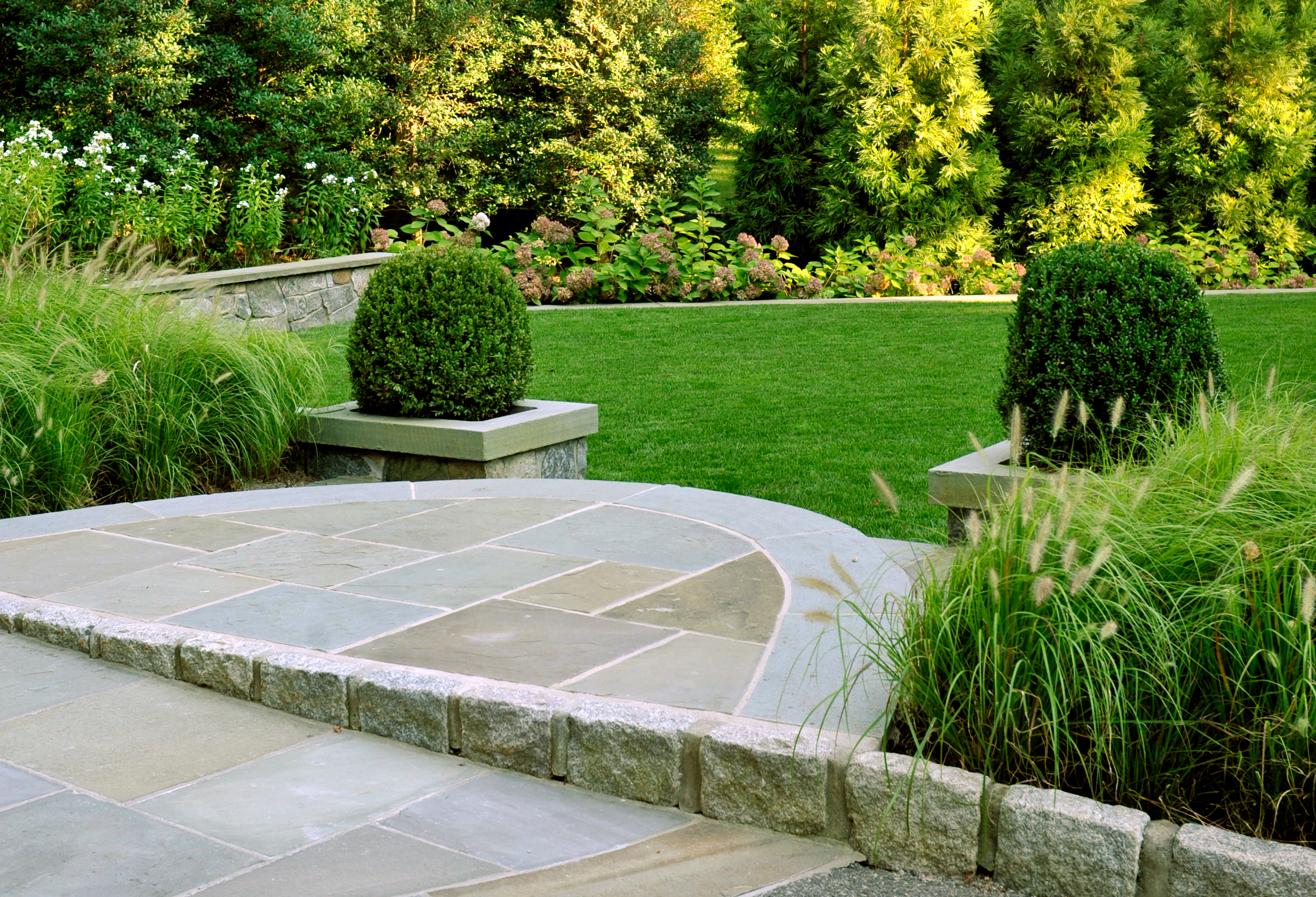 Private garden with stone patio and woodland plantings