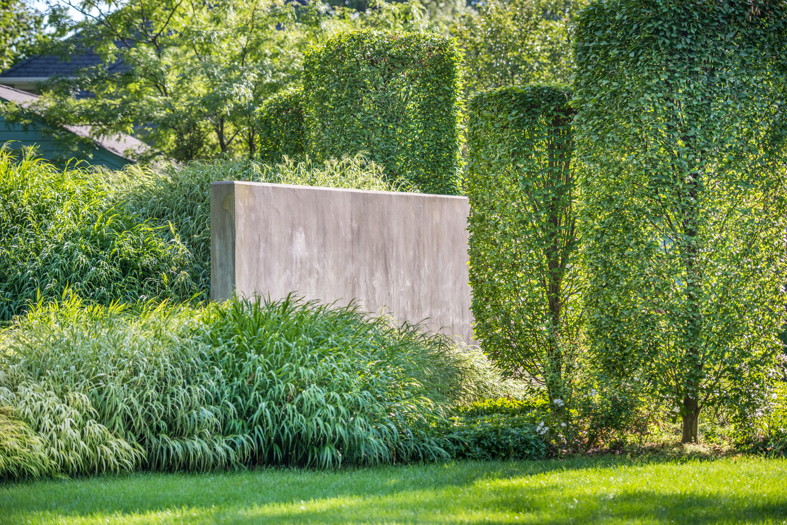 Concrete wall for dynamism and interest also serve to contain manmade berms