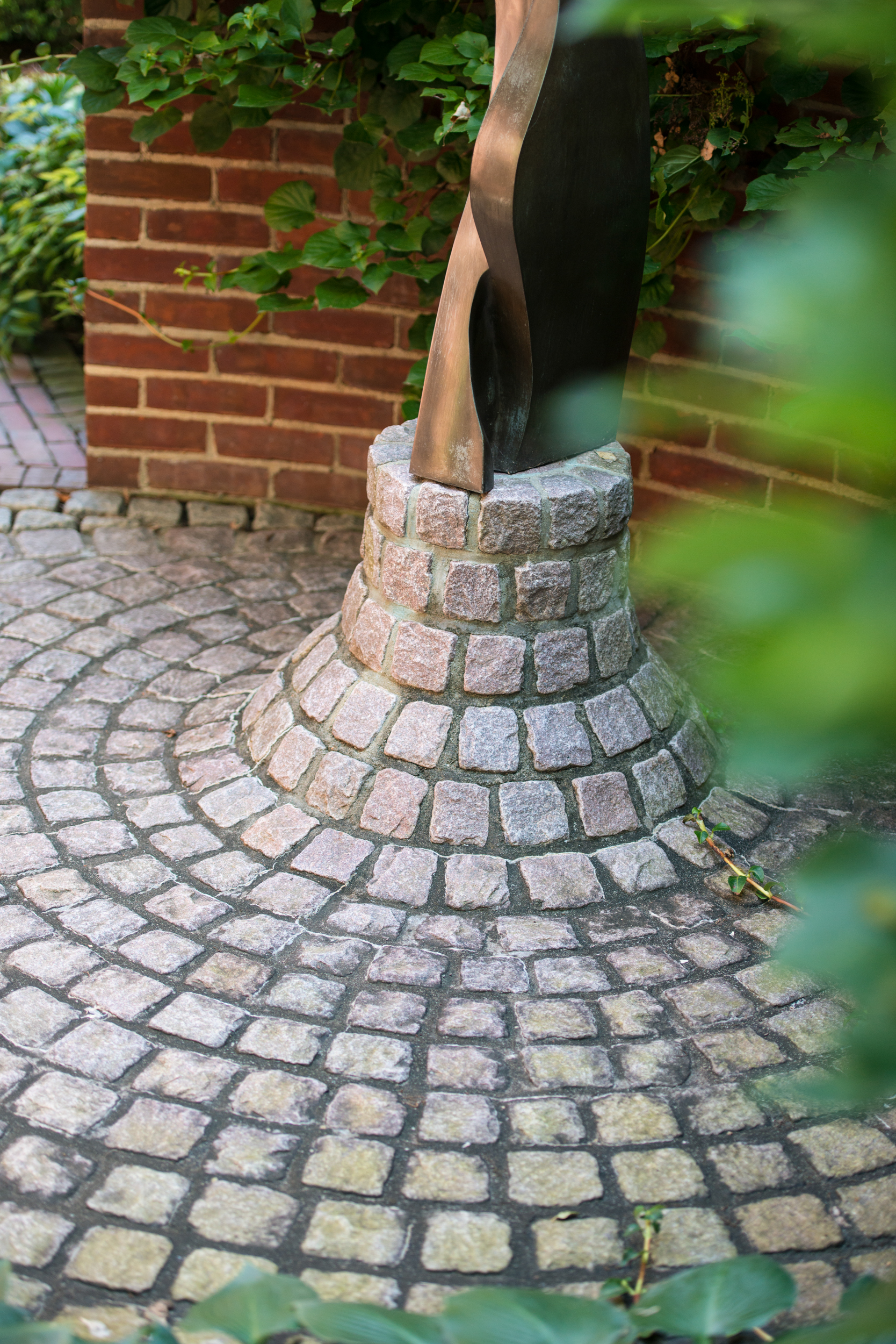 Cut garnite cobble stone pavers used as a support base for a sculptural piece