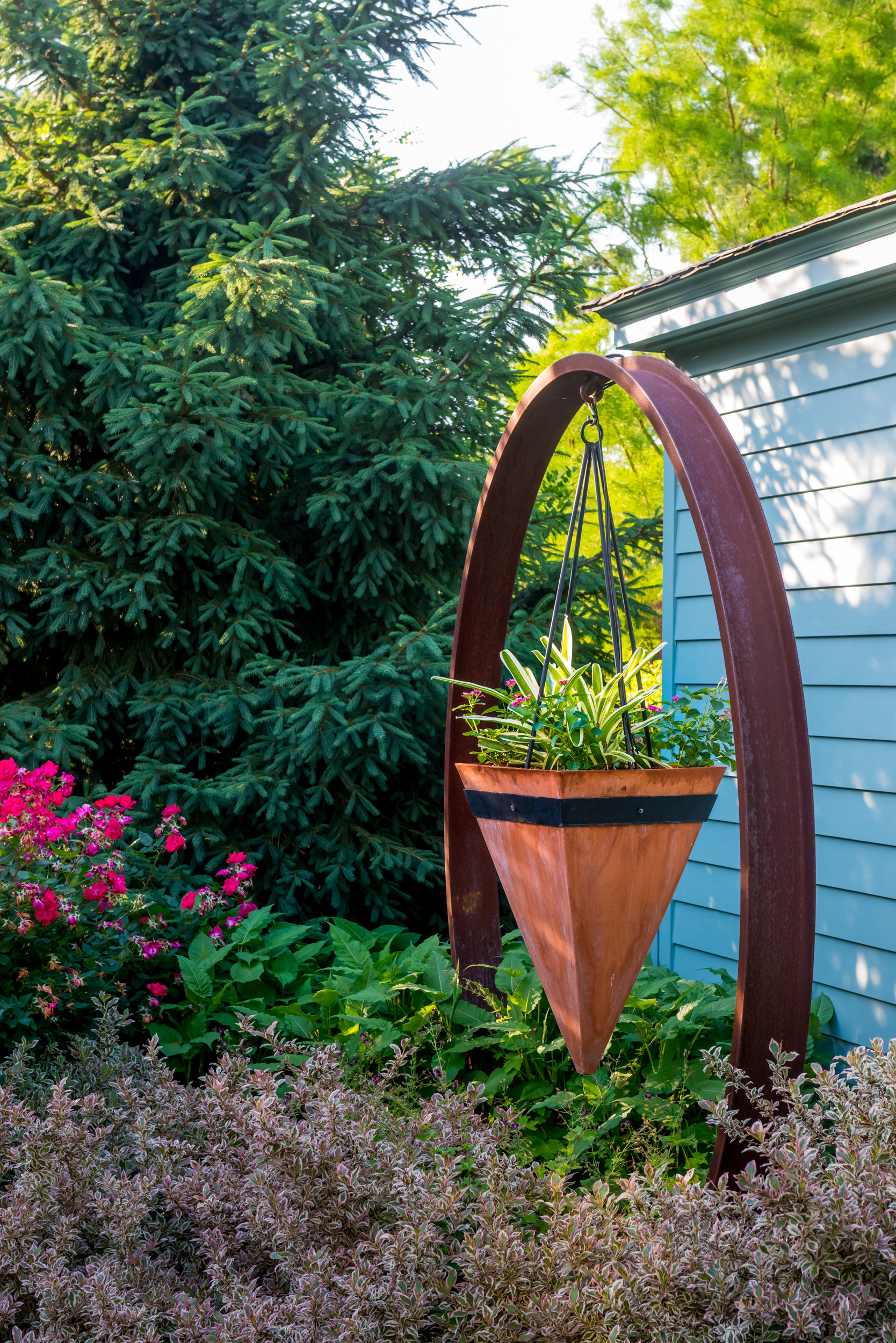 Sculptural corten hanging planter supported by a steel circular frame