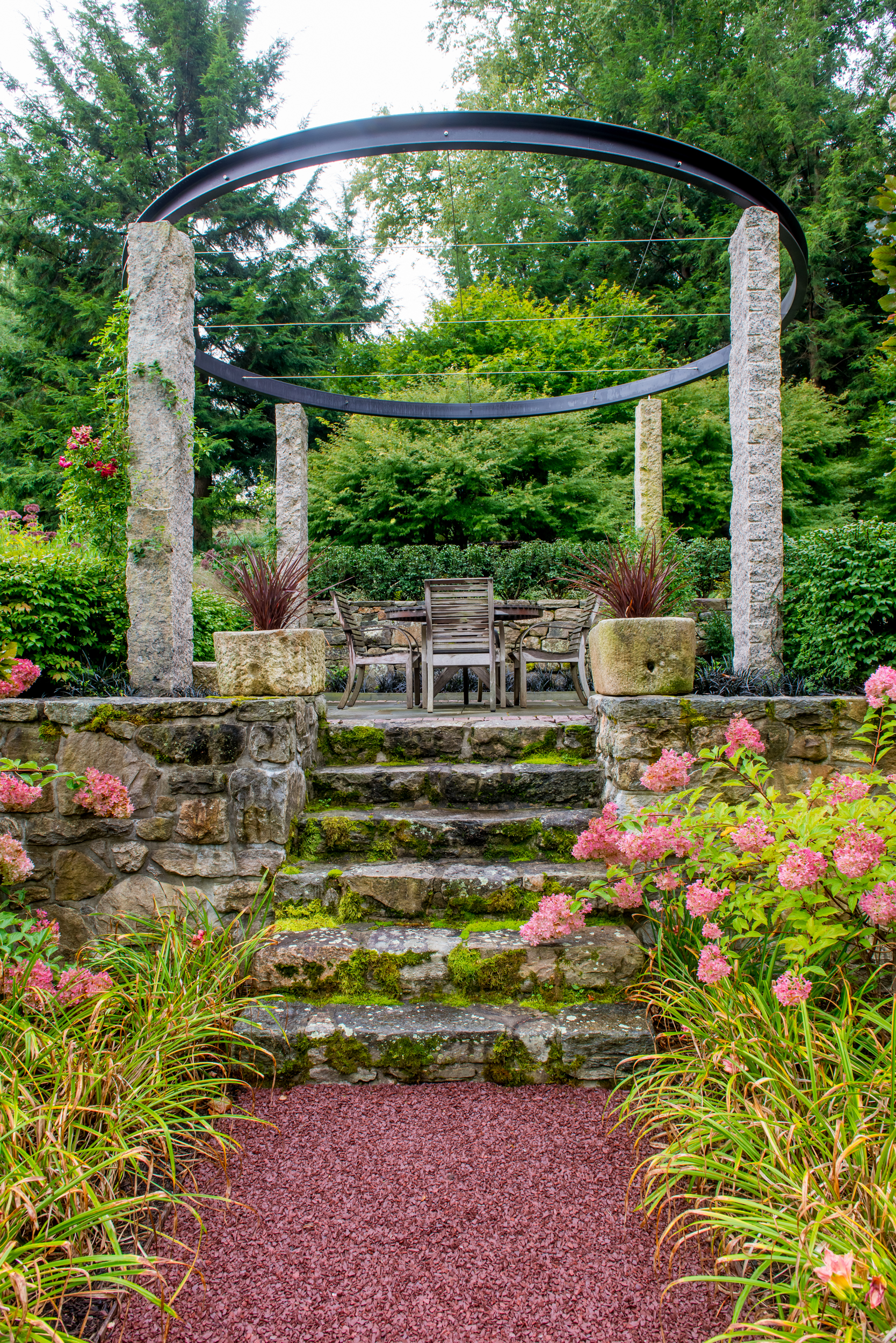 Steps leading to stone patio with circular steel arbor