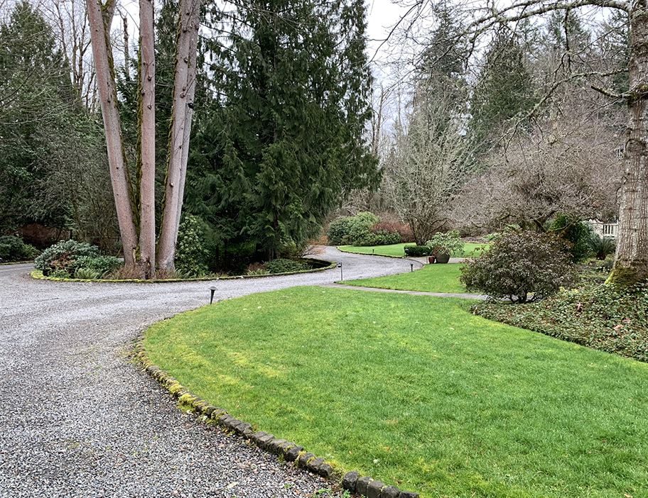 Currently the driveway includes a turnaround in front of the house with the only visible parking near the attached garage and the drive, which continues on to the guest house.