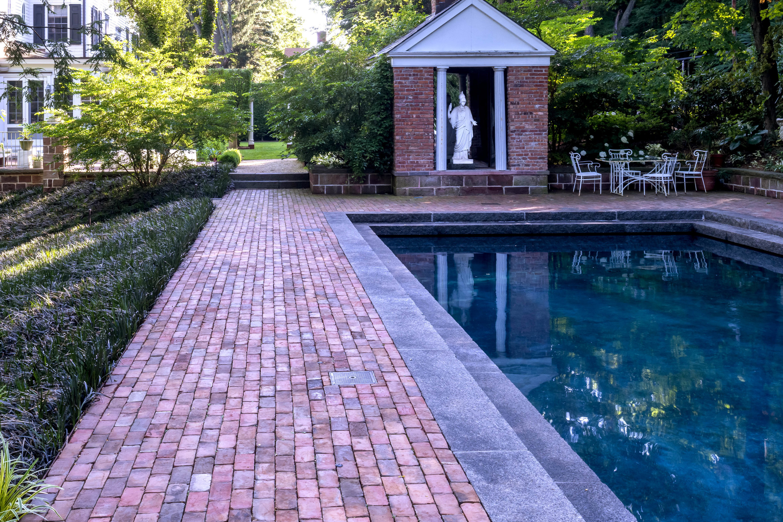 The brick pattern along the pool leads the eye to the folly and beyond at this Land Morphology designed  garden  in Piermont, NJ. Photo by  Rob Cardillo