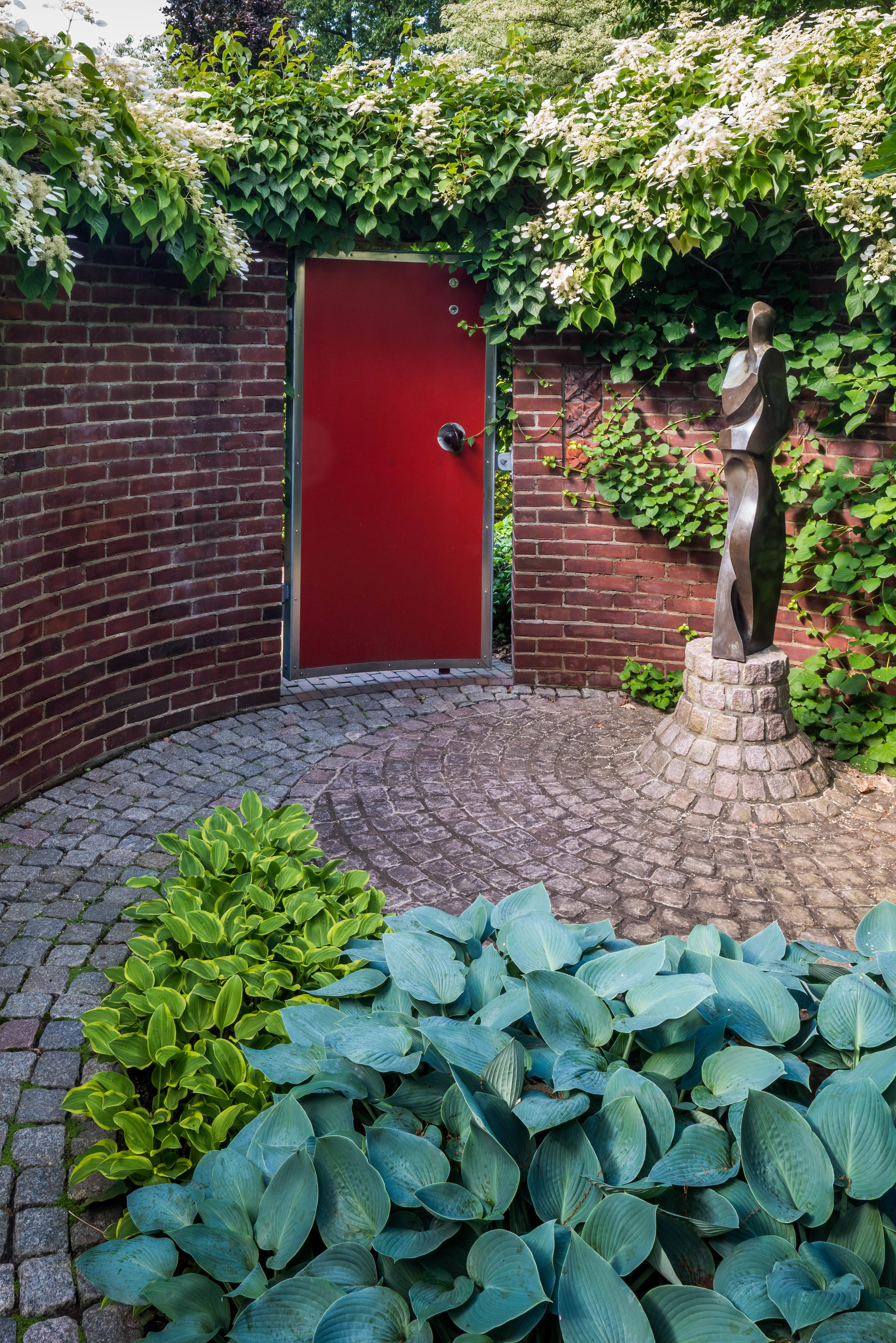 A brick wall encloses this courtyard, where spiraling cobbles coalesce at a sculpture at  Mountsier Garden  by Land Morphology.  Photo by  Rob Cardillo