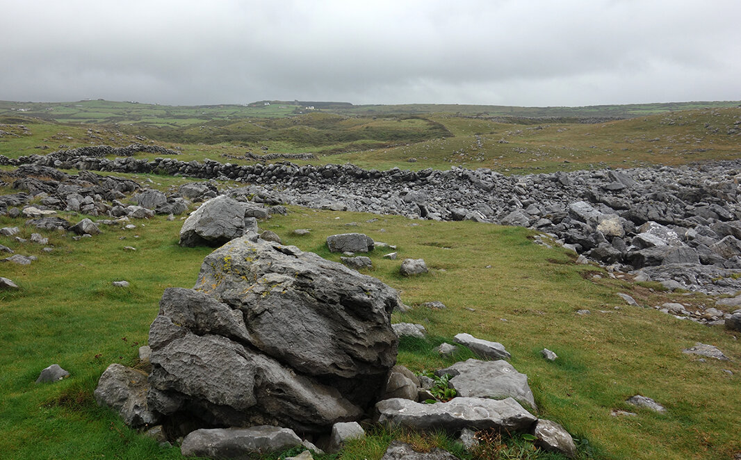 In The Burren, north of the Cliffs of Moher, Republic of Ireland, the rocky uplands provide plenty of material for building walls to keep grazing livestock confined. The stone walls appear to morph out of the earth and blend in with the naturally occurring erratics (large rocks) and other piles of stones.