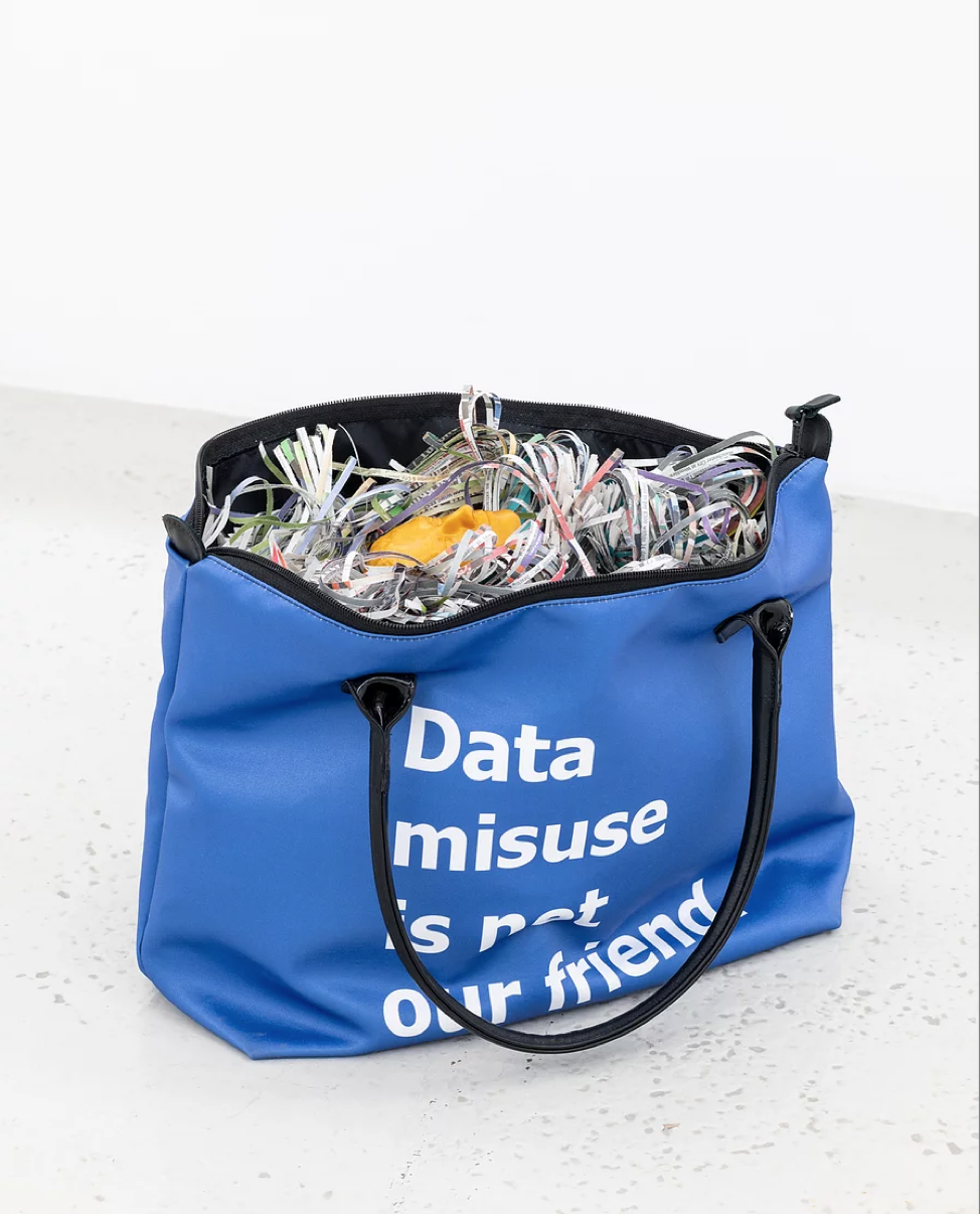 Unattended Bag , 2018, Custom printed zip top handbag, 3D printed ABS plastic, USB drive, downloaded Facebook data, shredded newspapers, 31 x 47 x 14.5 cm, Unique. Image courtesy of the artist and Annka Kultys Gallery.