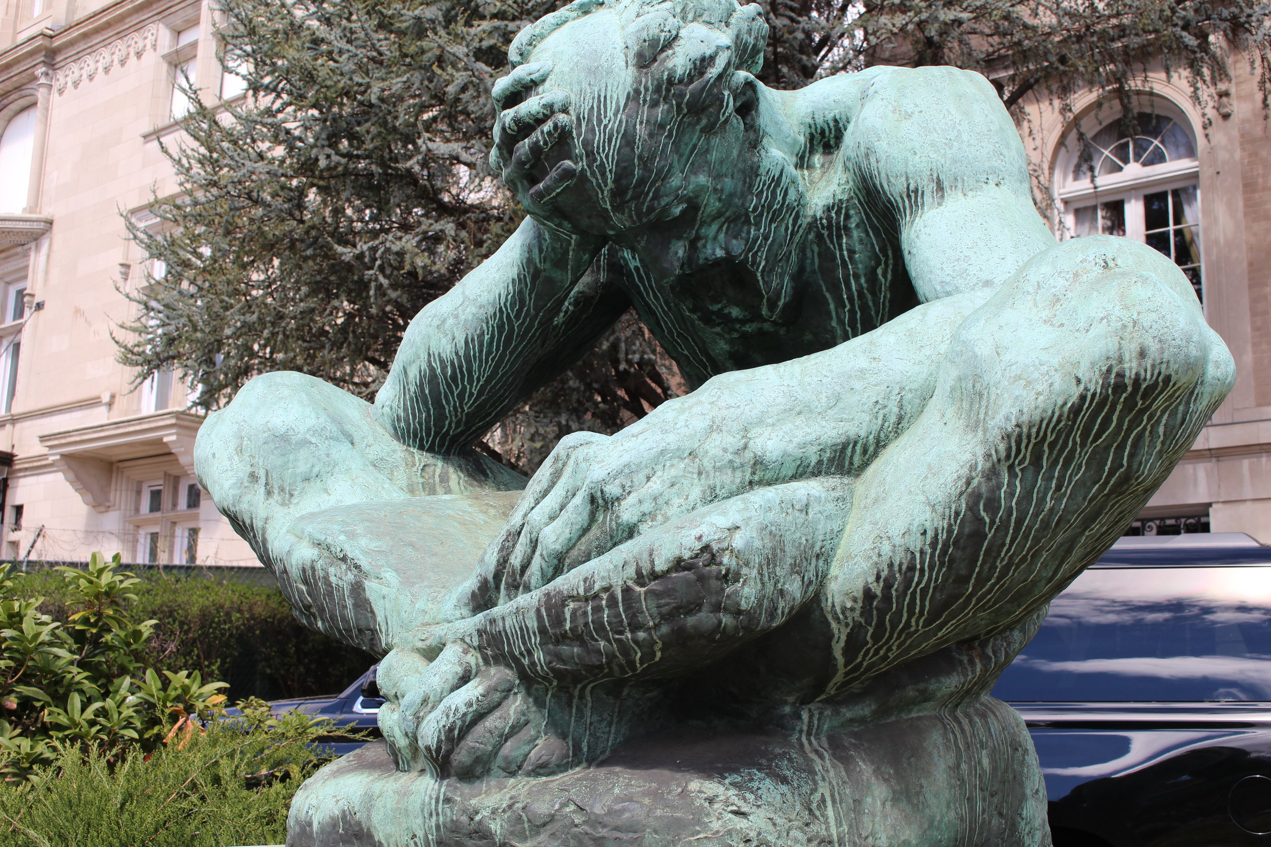 Sculpture of man reading a book with head in hand