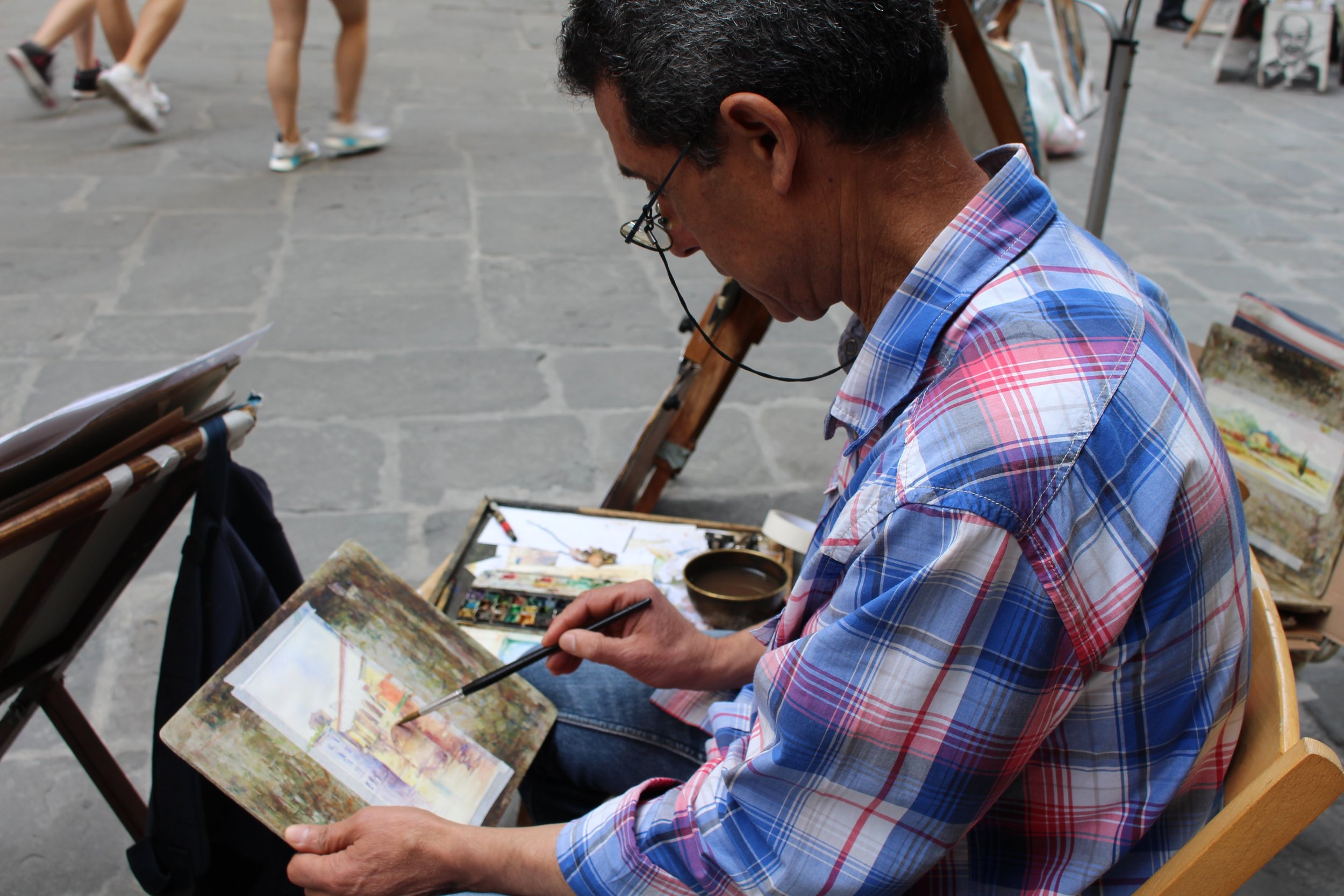 This was a kind hearted painter that saw my camera and said you can take a picture of me. He was painting outside the Uffizi in Florence.