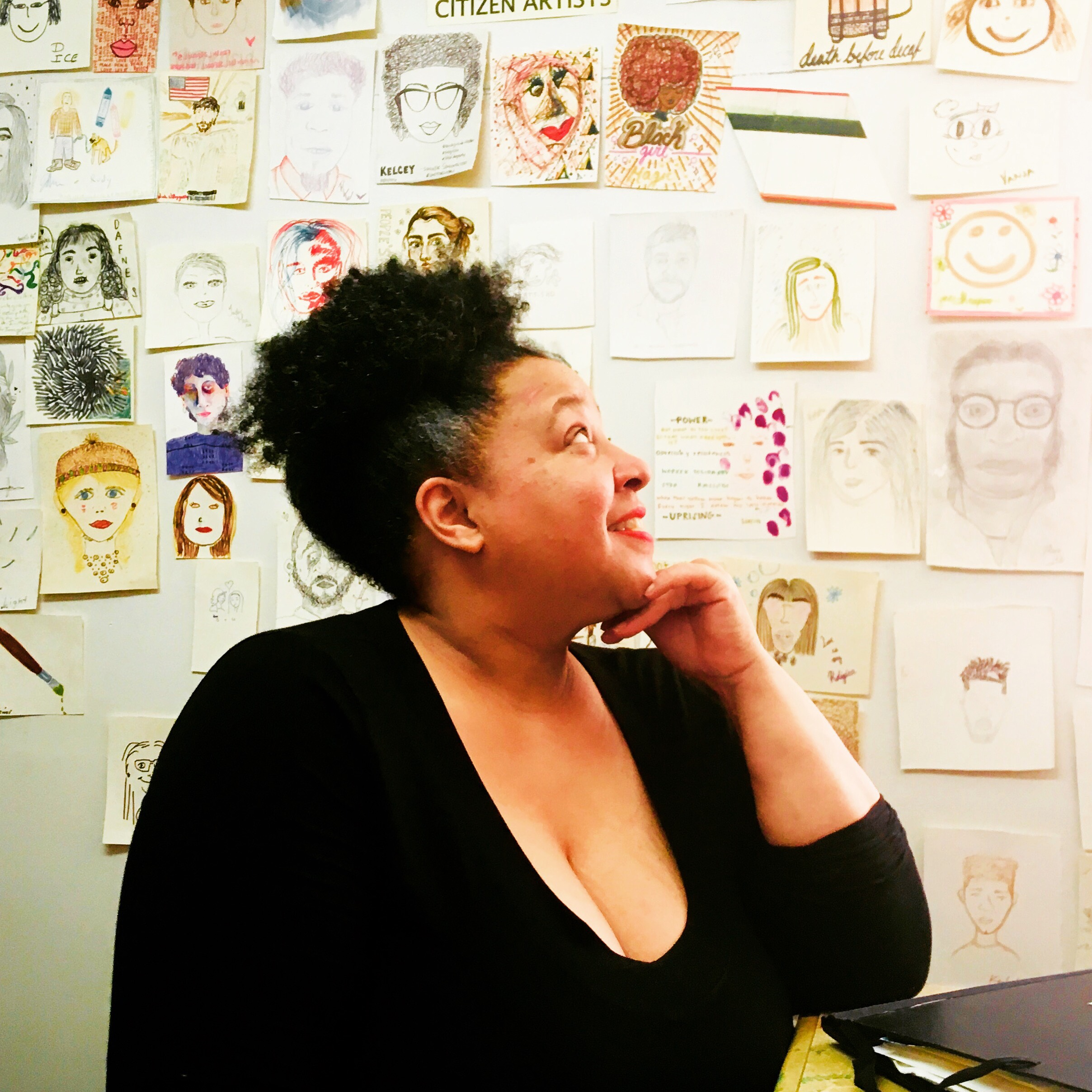 Karen in her studio inside The People's Perk surrounded by customer self portraits.