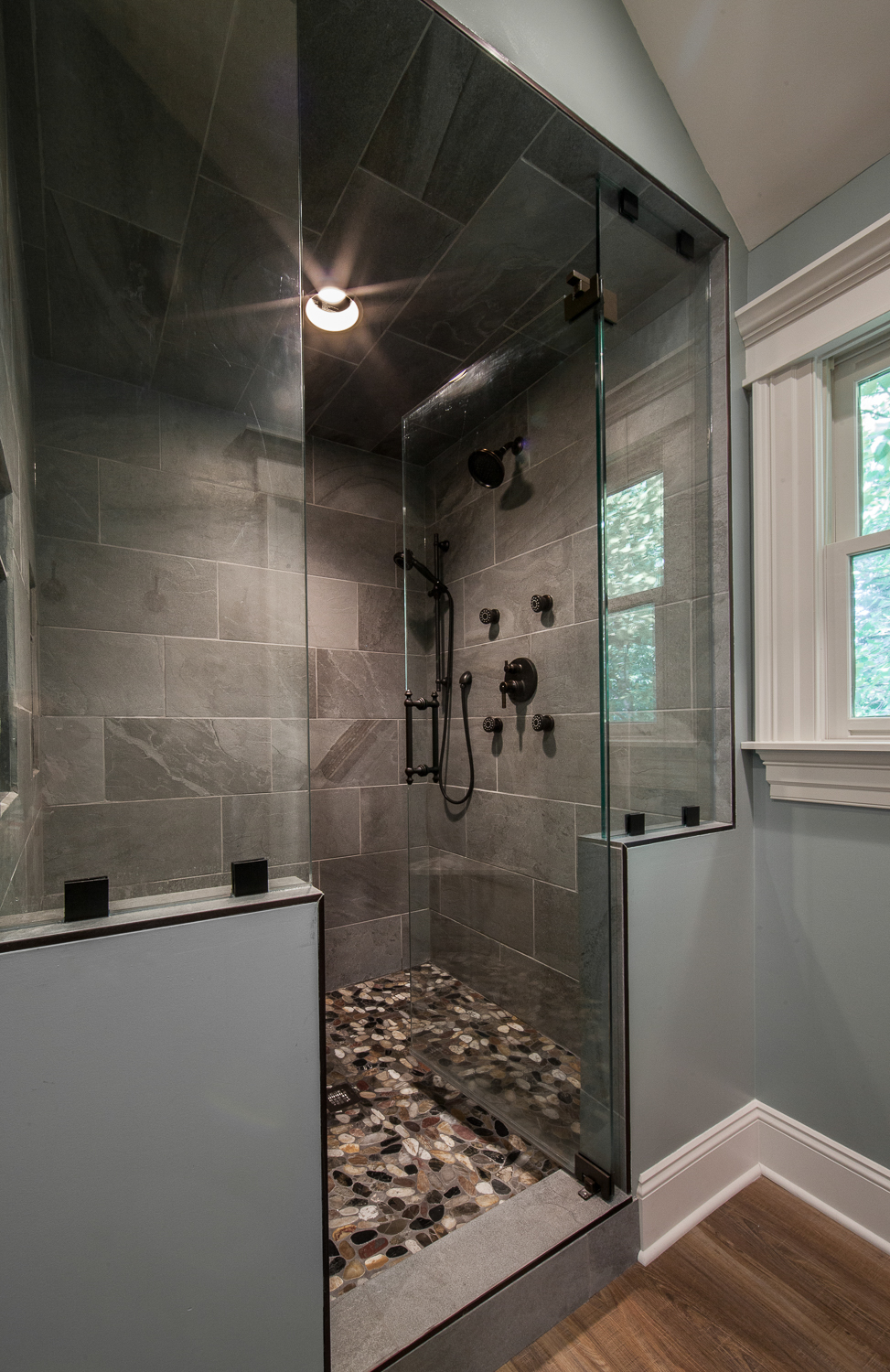 This shower is stunning! The slate tile give it a natural but contemporary vibe, and the stone pebble floor provides a spa-like experience. It's complete with 4 body sprays, a hand shower, and a shower head. The glass enclosure gives it a much more open feel compared to the walled-in shower that used to be in it's place.