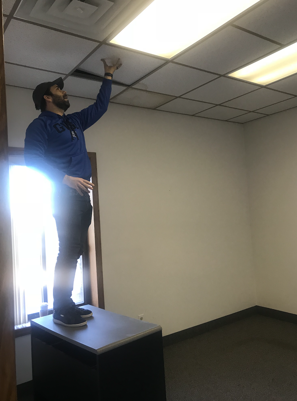 Before - Here's Justin removing a ceiling tile to see what was above the drop ceiling to know if we could remove it or not. This was a pivotal moment in the initial office tour.