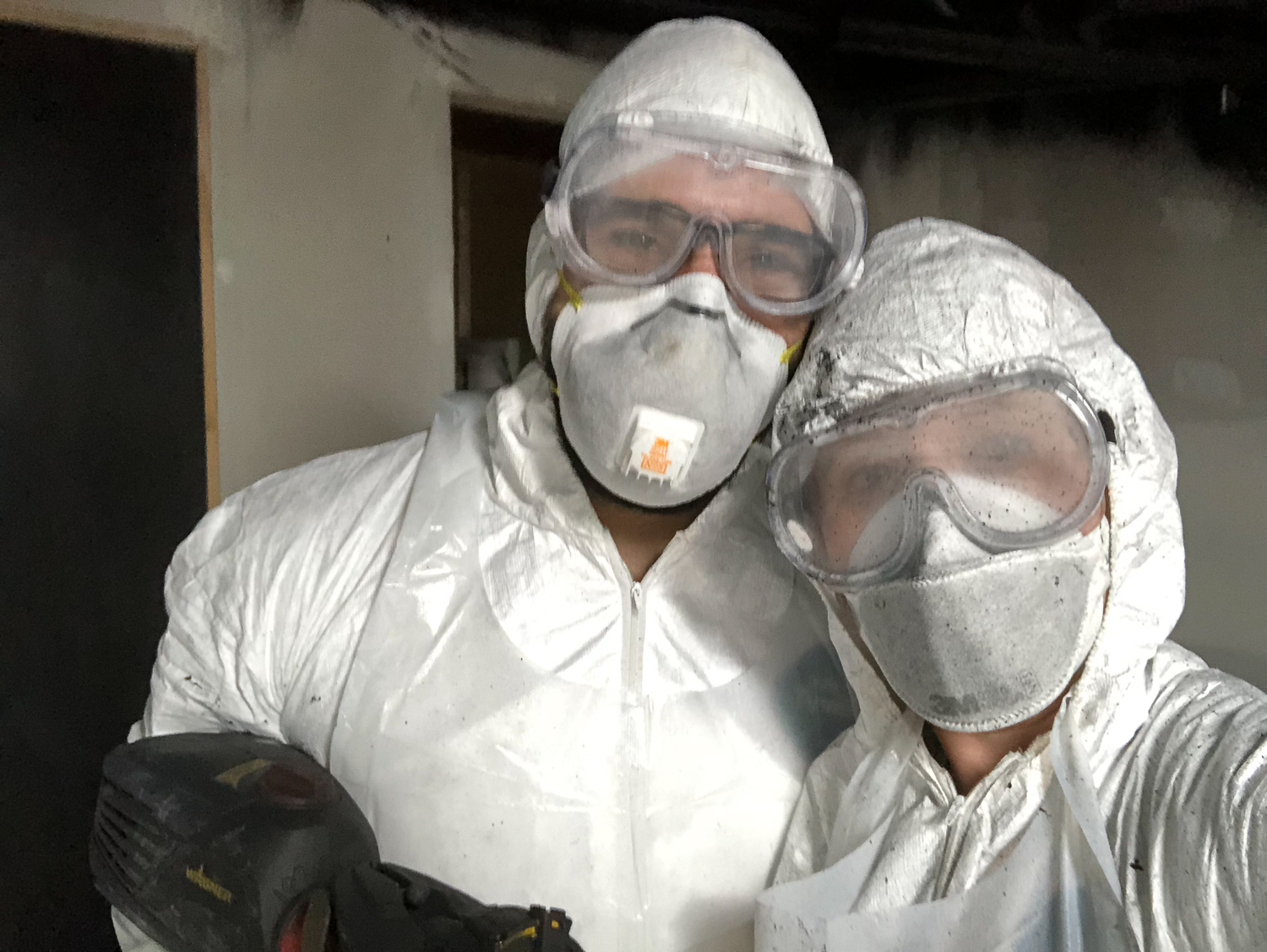 We decided to spray the ceiling black to hide all of the HVAC, electrical conduit, and plumbing that runs between the floor joists for the main level. These hazmat suits came in handy!