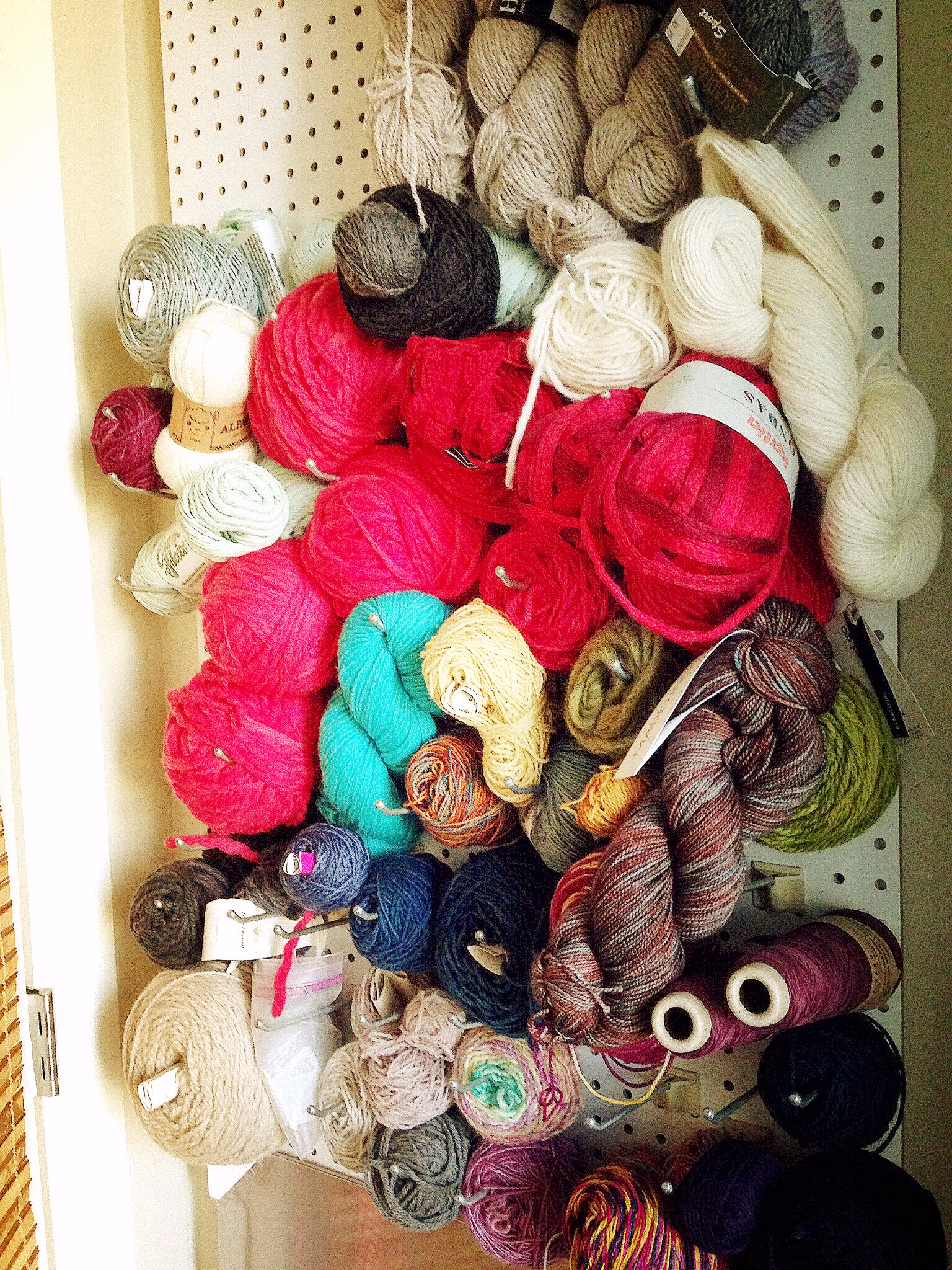 Yarn Wall! The #flufflyblondemonster created this removable peg board for me to store all of my yarn. It hides behind the door and also covers the fuse box for our apartment (which is why it had to be removable) It's a great way for me to visualize my yarn stash and plan projects.