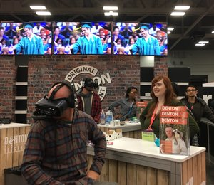 a person watching another person try out a virtual headset with a tv behind them