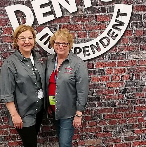 two people posing next to a discover denton logo on a fake brick wall