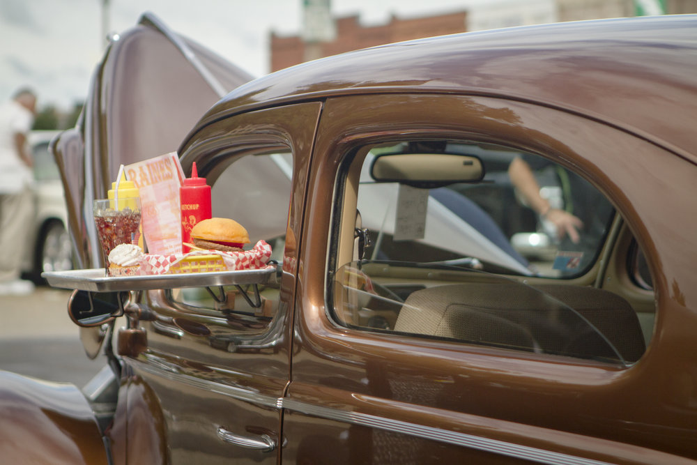 a classic car with a traditional movie tray rack on the window