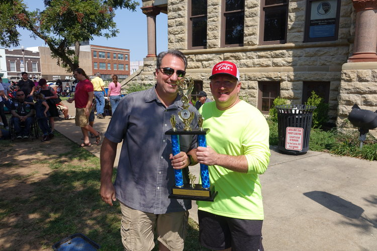 two men posing with a trophy