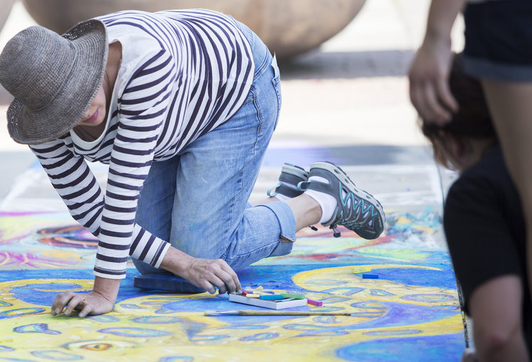 a person in a shirt and hat working on chalk art © Tammi Paul Photography