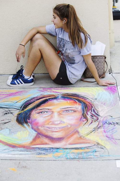 A girl posing with her chalk portrait© Tammi Paul Photography
