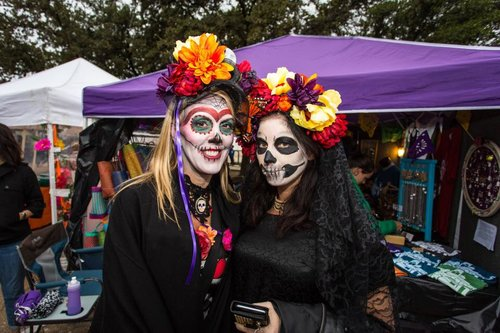 two women painted like sugar skulls posing in front of vendor booths