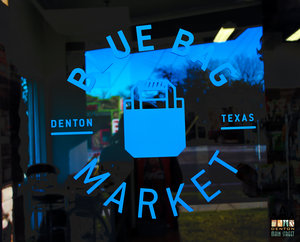 a picture of a blue logo that says blue bag market on a door