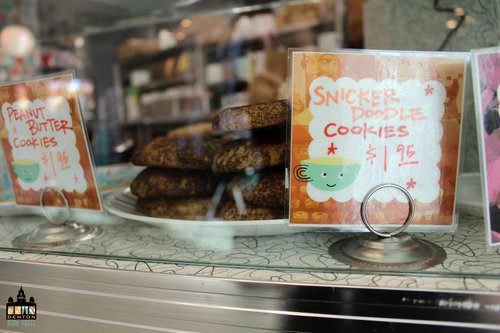 a picture of a plate of cookies and a cookie sale sign