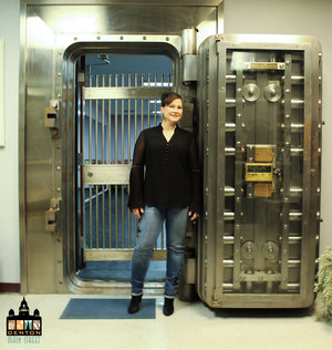 a picture of a person standing next to a bank vault door