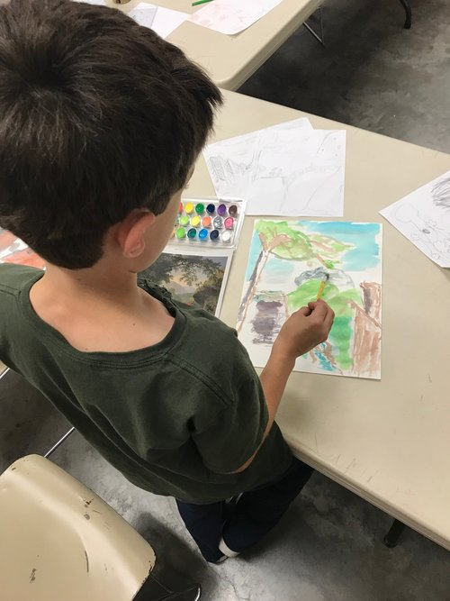 a picture of a child painting with watercolors