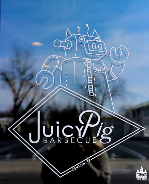 a picture of the door of juicy pig with their robot pig logo