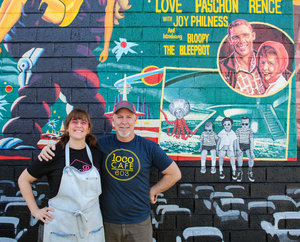 a picture of two people standing next to a mural