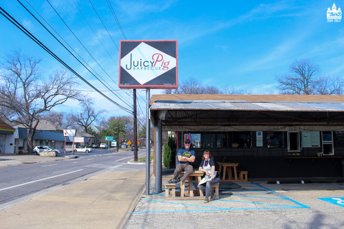 a pictureo f two people sitting outside of the juicy pig restaurantjpg