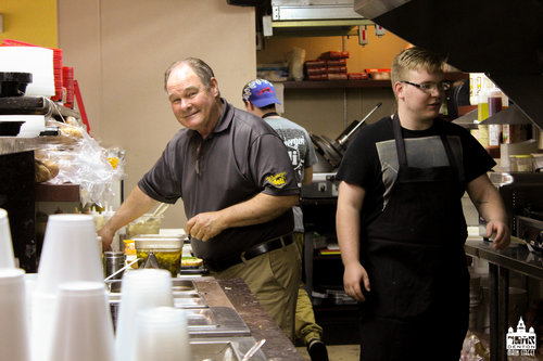 a picture of a man and some staff inside a sandwich shop working