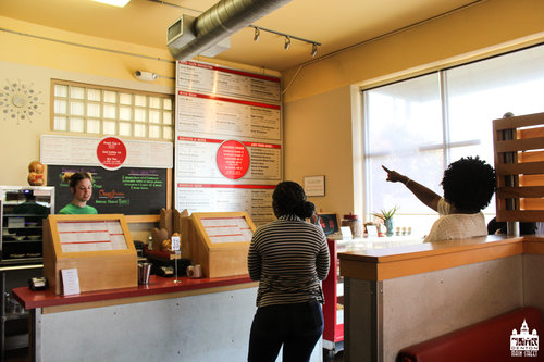 a picture of people ordering at a cashier inside a restaurant in front of a large menu