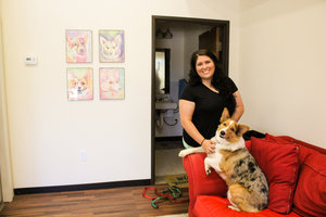 a picture of a woman and her dog on a red couch