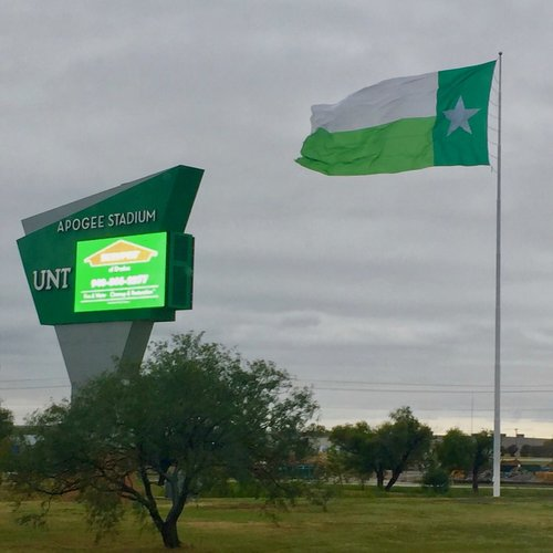 a picture of a green UNT flag and the apogee stadium sign outside.