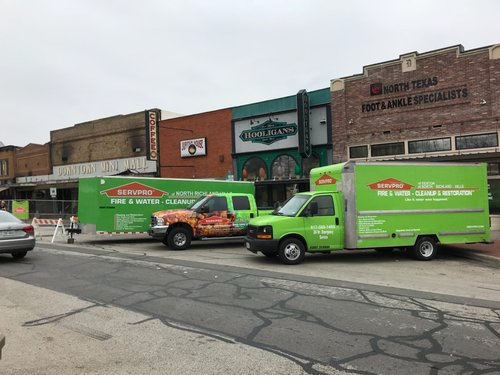 a picture of several servpro trucks parked in the street of the downtown denton square