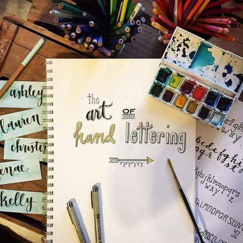 "a picture of a notebook that says ""the art of hand lettering"" with art pencils near it.jpg"
