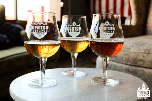 a picture of three denton county brewing company glasses with a small amount of beer in each glass