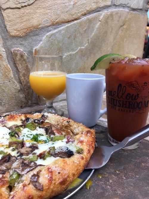 a picture of a vegetable pizza and bloody mary, a mimosa and cup of coffee