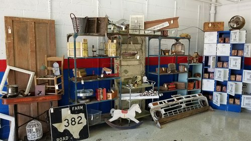 inside of a vintage store with shelves of products like signs and trinkets.