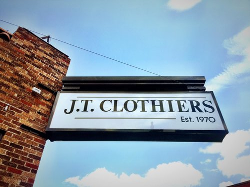 a picture of the jt clothiers est. 1970 sign on a brick wall against the daytime skyl
