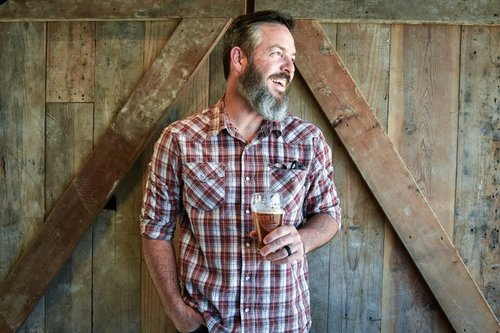 a man smiling looking to the side wearing a red plaid shirt holding a beer and standing against a barn door.