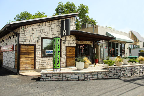 a picture of the storefront of a plant shop called flowergarden118 with a fountain outside of it.