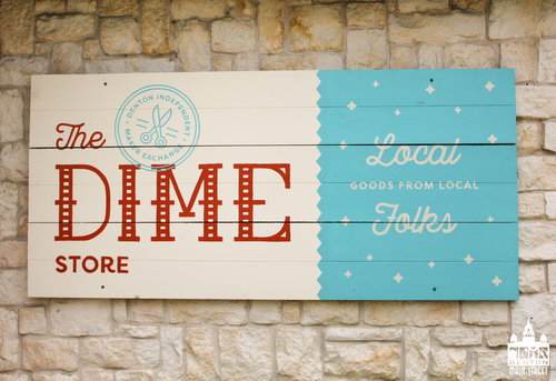 "a picture of a blue and white wooden sign that says ""the dime store - local goods from local folks"""
